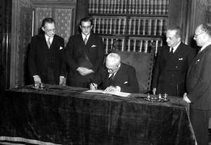 Il Capo provvisorio dello Stato De Nicola firma la Costituzione. A sinistre De Gasperi Presidente del Consiglio, a destra il comunista Scoccimarro Presidente dell'Assemblea Costituente